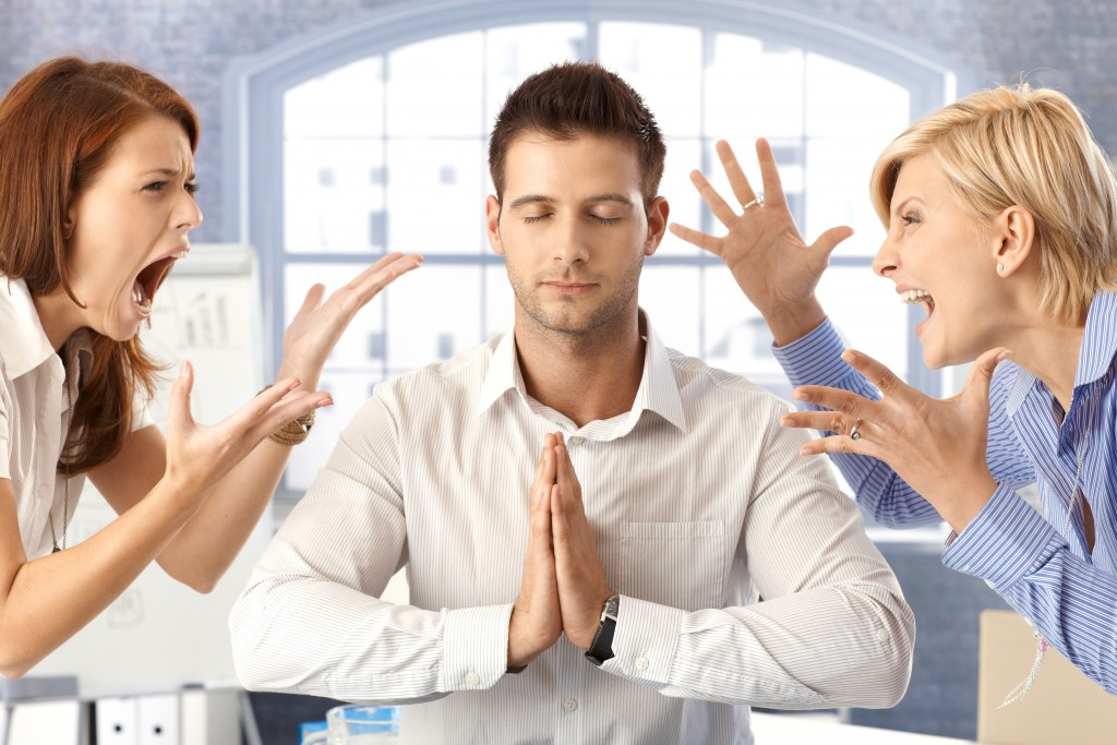 Meditating closed eye businessman in office with arguing colleag